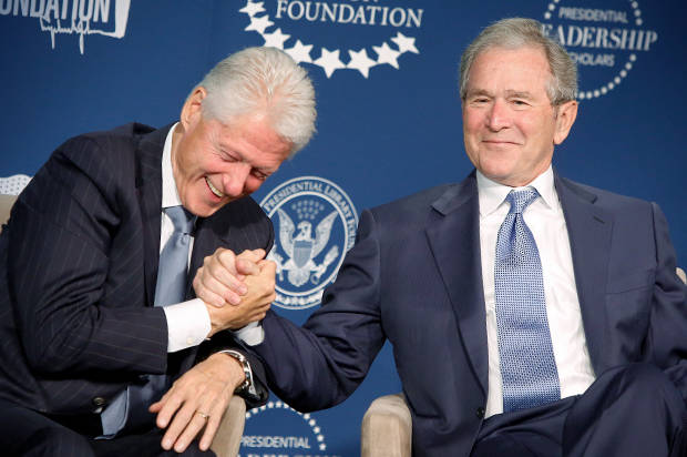 Former U.S. presidents Bill Clinton and George W. Bush shake hands and joke on stage during a Presidential Leadership Scholars program event at the Newseum in Washington